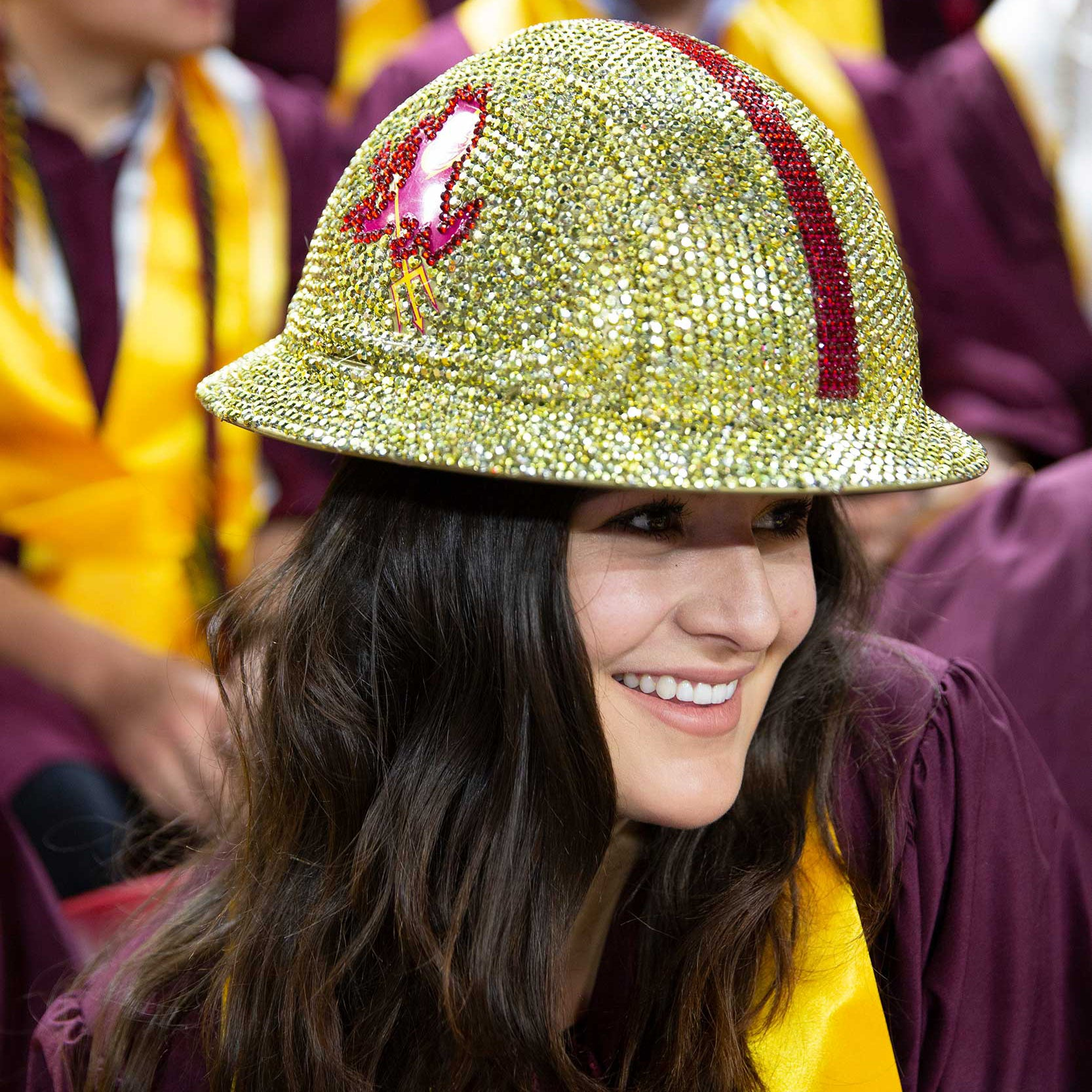 A construction graduate smiles as she shows off her bedazzled ASU hard hat