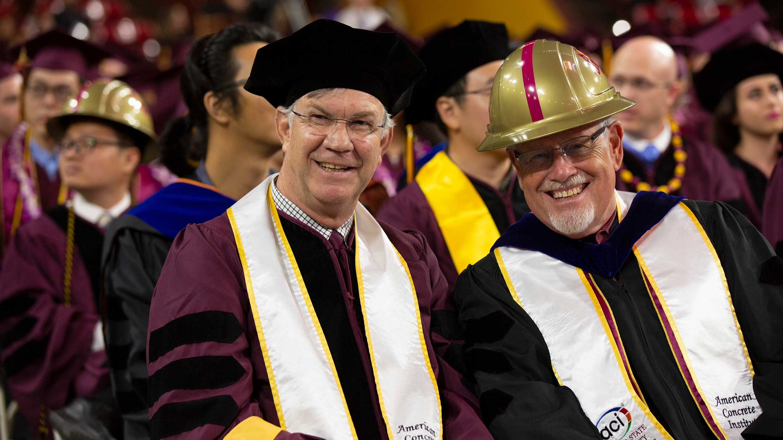 Richard Standage and Jim Ernzen smile for the camera at Convocation, dressed in their full regalia