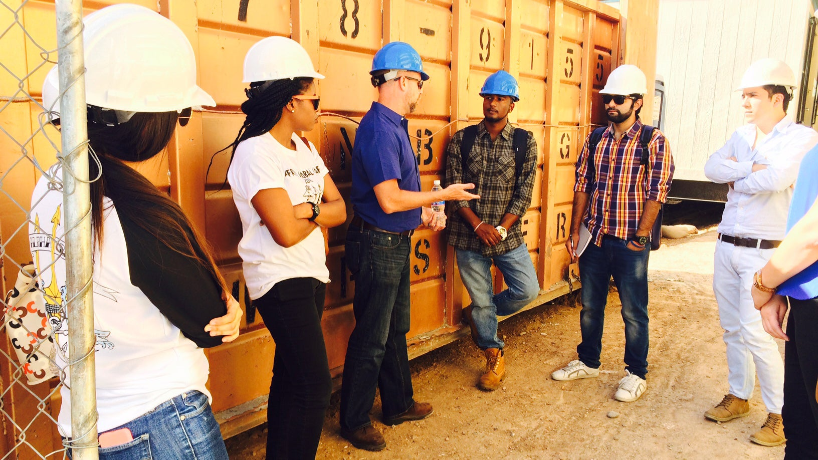 A group of students listens to an industry professional at a construction site