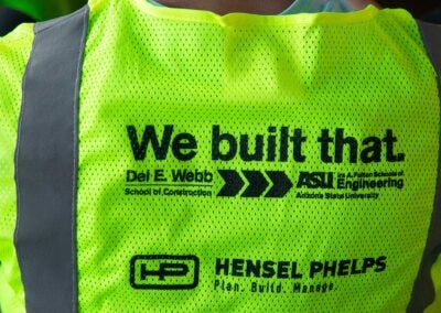 "Construction vest with ""We built that."" logo and sponsorship by Hensel Phelps"
