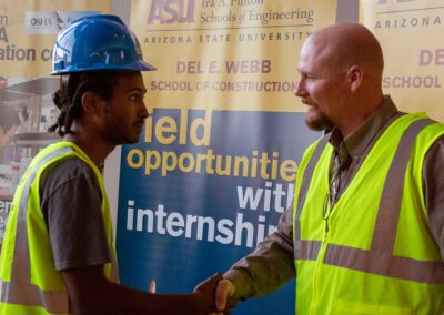An industry professional shakes hands with a DEWSC student at the vesting ceremony during Safety Week