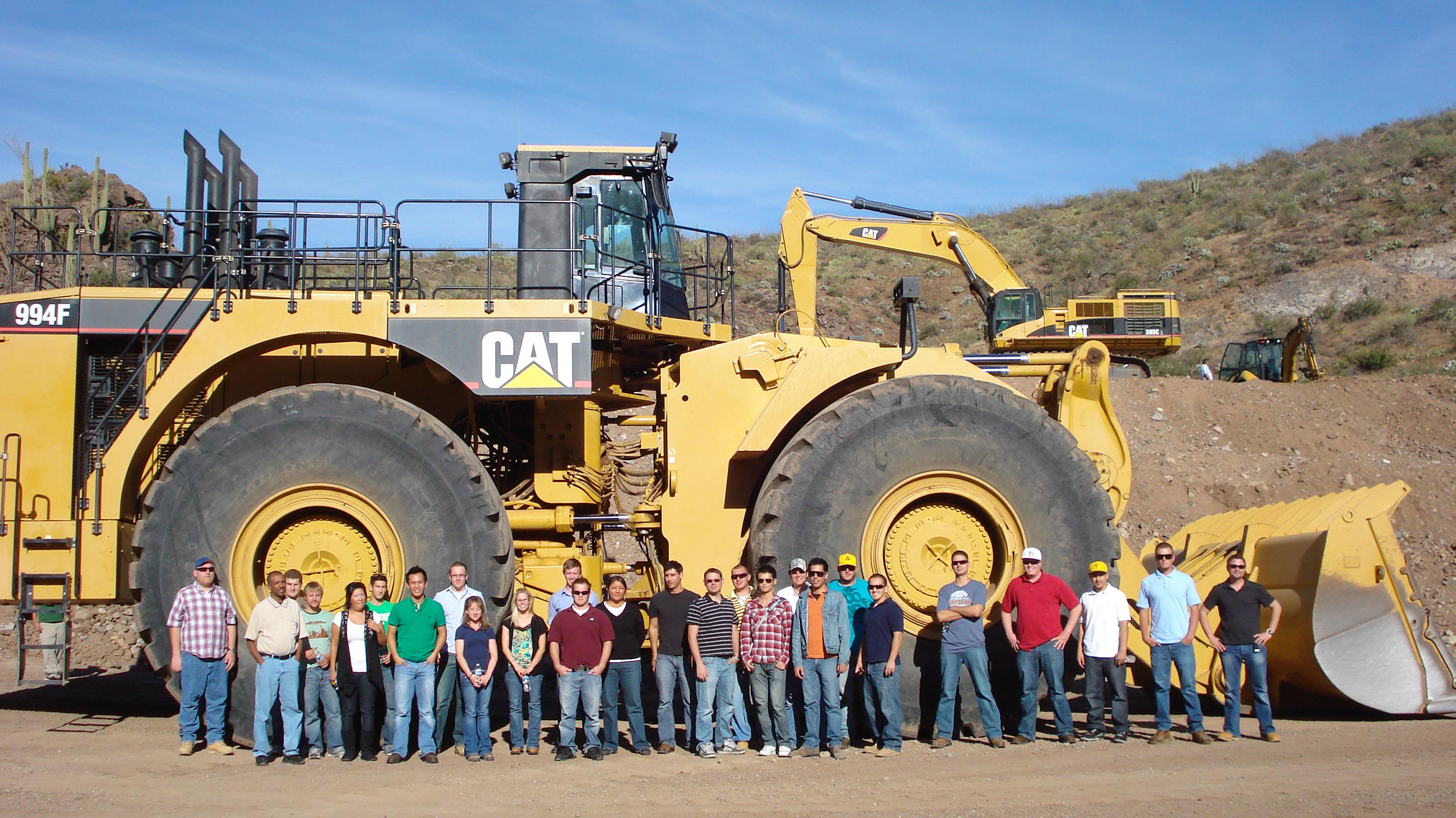 A group of students and construction professionals stand before an enormous CAT construction vehicle