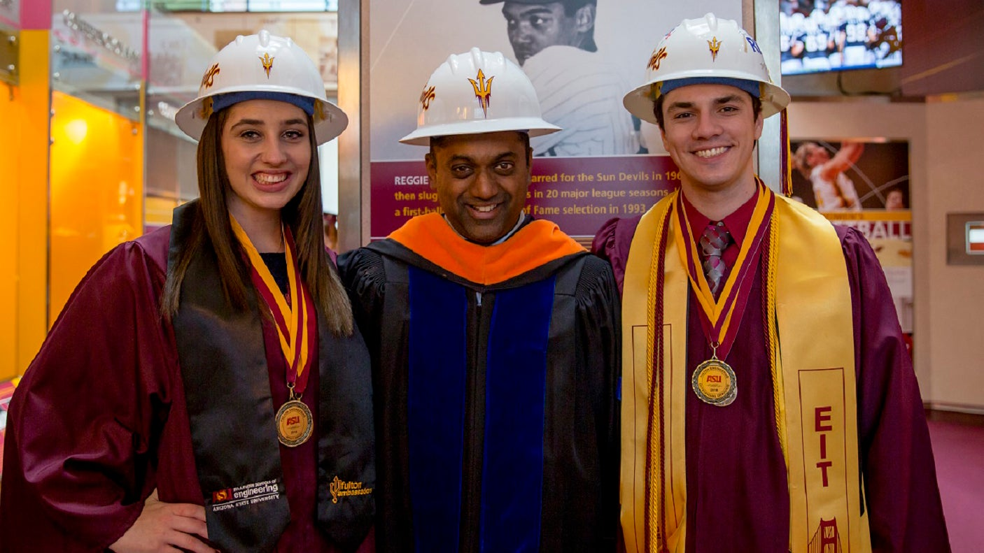 Two DEWSC graduates stand with Prof. Sam Ariaratnam